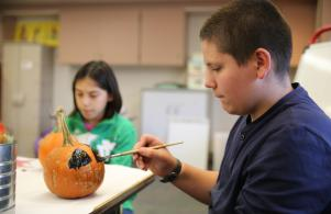 Walt Disney students painting pumpkins