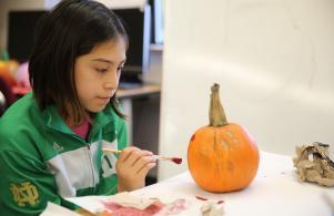 Walt Disney students painting pumpkins